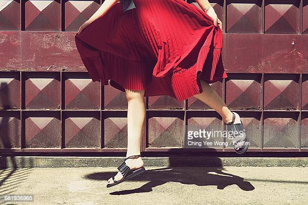 low section of woman holding dress while jumping against metal gate - sandal stock pictures, royalty-free photos & images