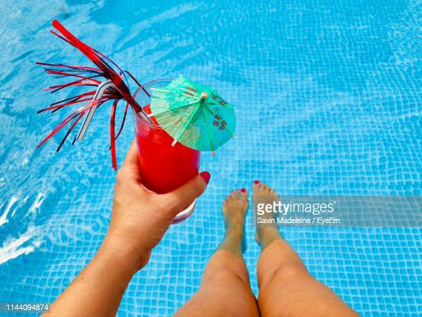 low section of woman holding drink while sitting by swimming pool - lady madeleine stock-fotos und bilder