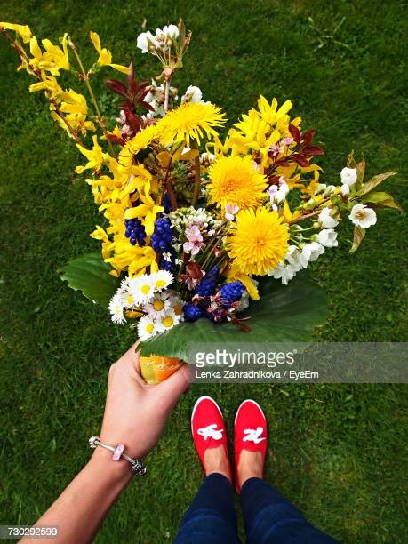 Low Section Of Woman Holding Flower Bouquet