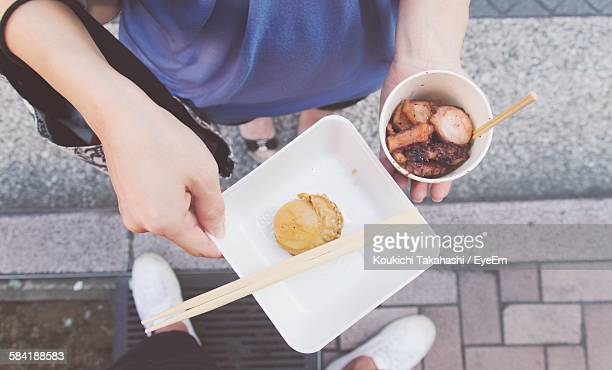 Low Section Of Woman Holding Food On Street