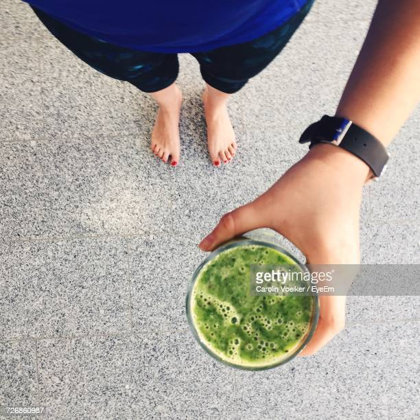 Low Section Of Woman Holding Green Smoothie While Standing On Footpath