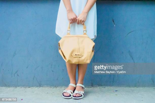 Low Section Of Woman Holding Handbag While Standing In Front Of Blue Wall