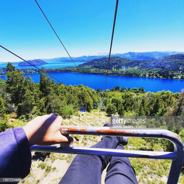 low section of woman holding handle while sitting in cable car against river - bariloche stock pictures, royalty-free photos & images
