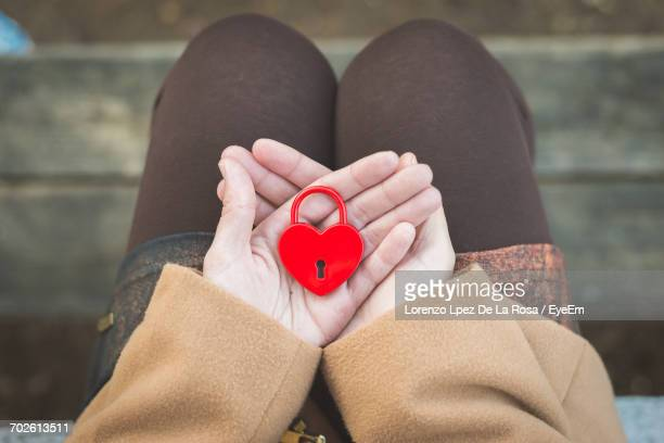 Low Section Of Woman Holding Heart Shape Padlock