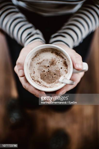 low section of woman holding hot chocolate at home - hot chocolate stock pictures, royalty-free photos & images