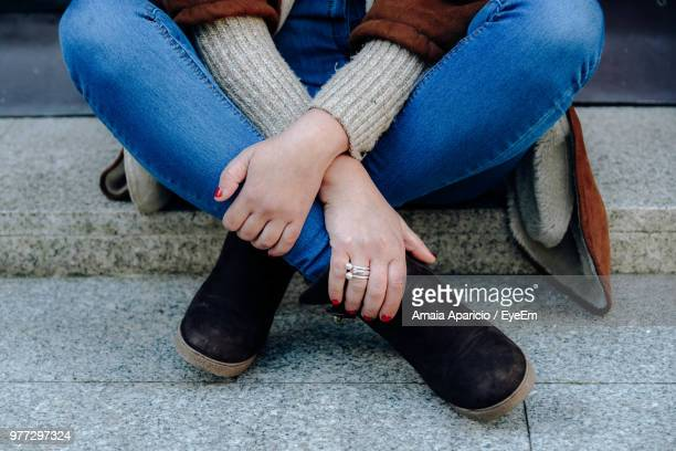 low section of woman holding legs while sitting on footpath - hands in her pants - fotografias e filmes do acervo