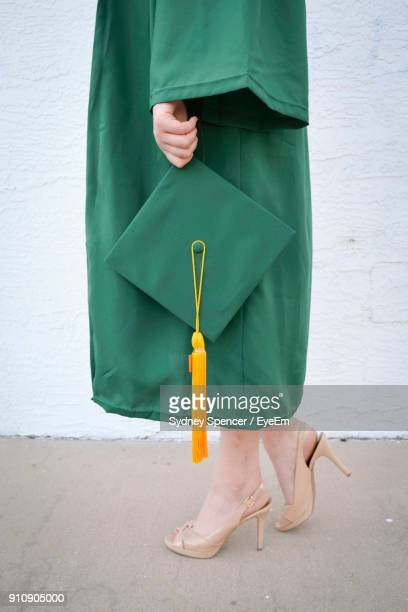 low section of woman holding mortarboard while standing on footpath - graduation gown stock pictures, royalty-free photos & images