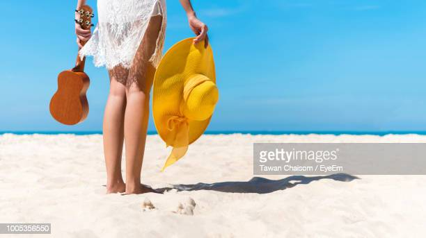 Low Section Of Woman Holding Musical Instrument And Hat On Sand At Beach Against Sky