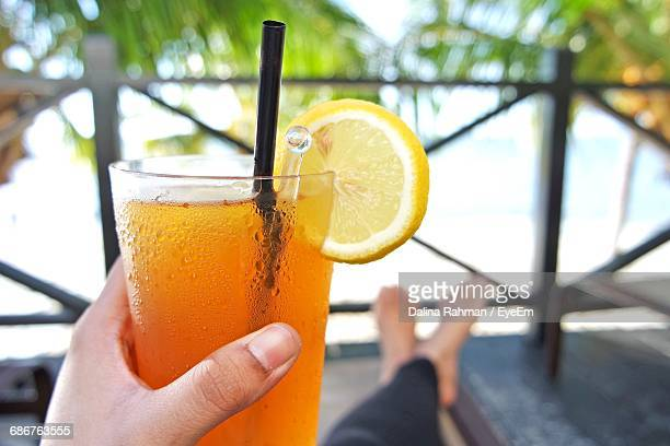 Low Section Of Woman Holding Orange Drink