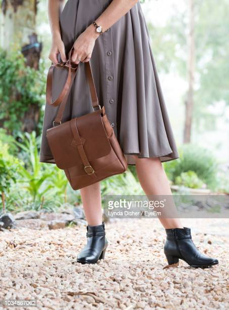 low section of woman holding purse while standing on field at park - leather purse stock pictures, royalty-free photos & images