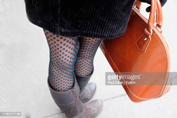 low section of woman holding purse while standing on footpath - nylon feet stockfoto's en -beelden