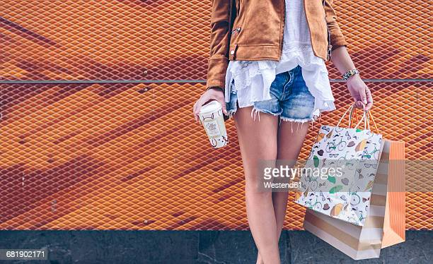 Low section of woman holding shopping bags and takeaway coffee