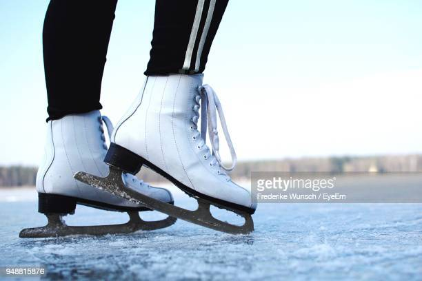 low section of woman ice skating on rink against sky - ice skate stock pictures, royalty-free photos & images