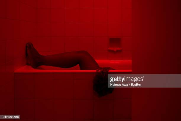 low section of woman in bathtub - red tub photos et images de collection