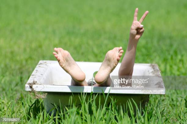 Low Section Of Woman In Bathtub Showing Victory Sign On Grassy Field