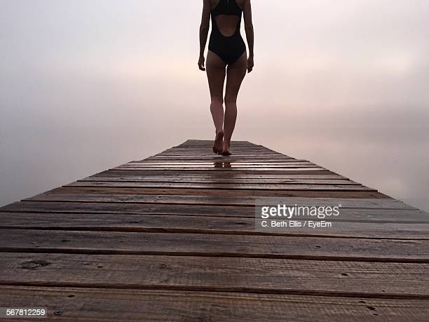 low section of woman in bikini walking on pier against cloudy sky - femme fatale stock photos and pictures