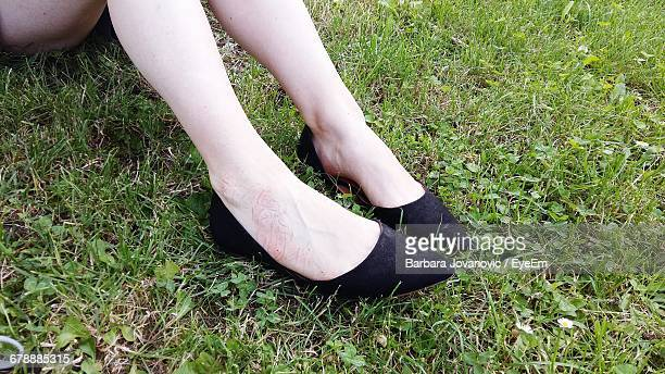 Low Section Of Woman In Black Flat Shoes On Grassy Field