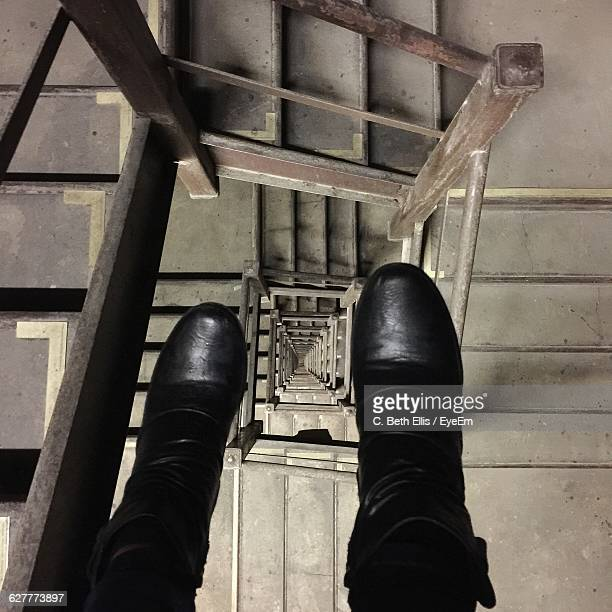 Low Section Of Woman In Black Leather Boot Over Spiral Staircase