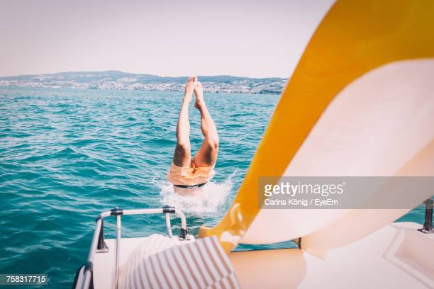low section of woman in boat sailing on sea against clear sky - wasserfahrzeug stock-fotos und bilder