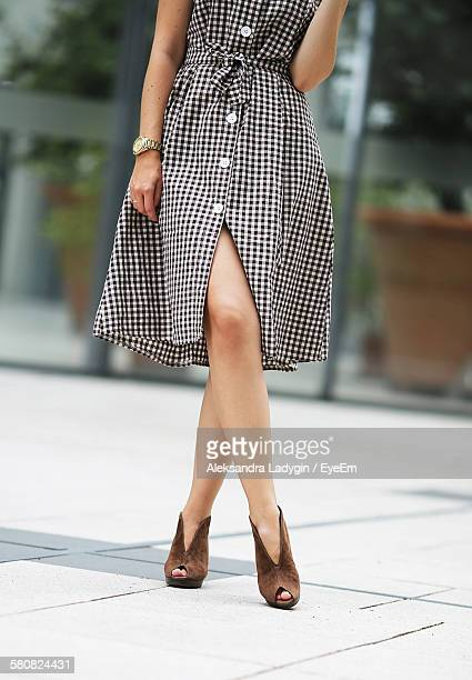 Low Section Of Woman In Checked Pattern Dress Standing On Street