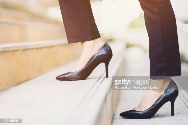 low section of woman in high heels on staircase - human foot stock pictures, royalty-free photos & images