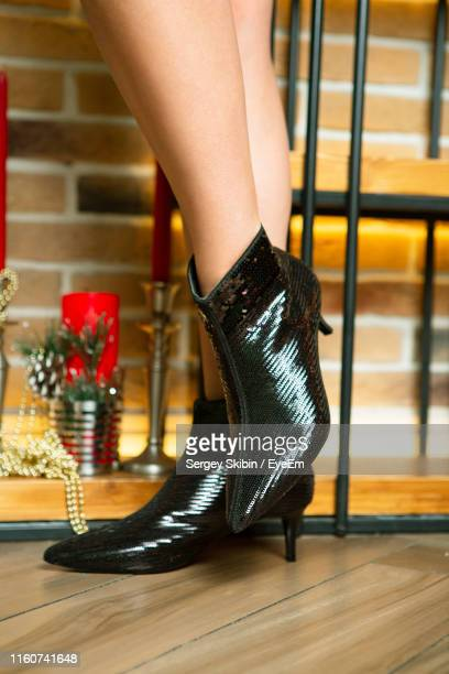 low section of woman in high heels standing on hardwood floor - bottes noires photos et images de collection