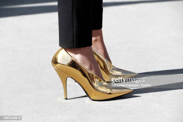 low section of woman in high heels standing on road - talons hauts photos et images de collection