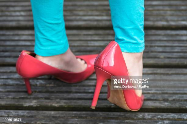 low section of woman in high heels standing outdoors - pump dress shoe stock pictures, royalty-free photos & images