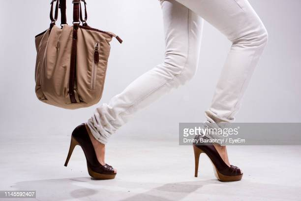 low section of woman in high heels with bag while walking against white background - partie inférieure photos et images de collection