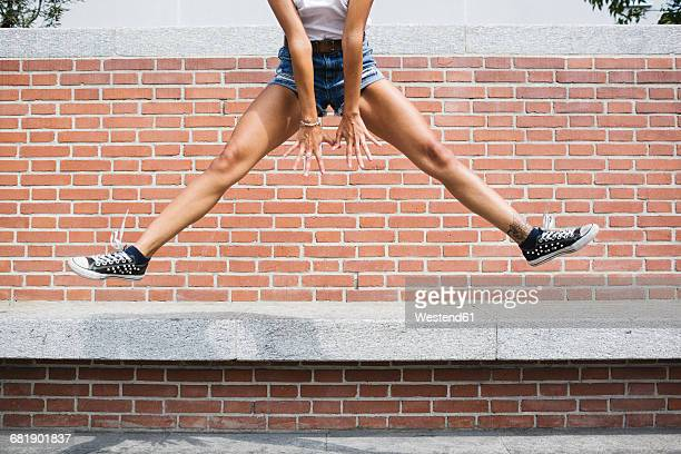Low section of woman in hot pants jumping at brick wall