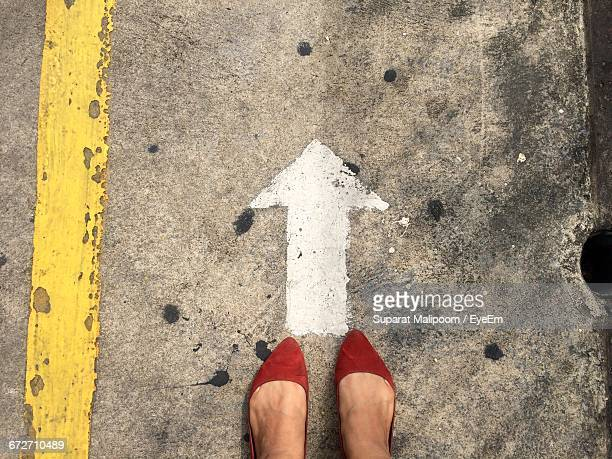 Low Section Of Woman In Red Flat Shoe Standing By Arrow Sign On Road
