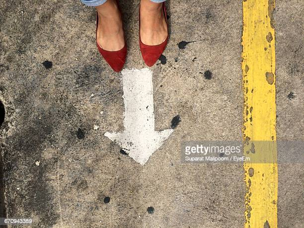 Low Section Of Woman In Red Flat Shoe Standing In Front Of Arrow Sign On Road