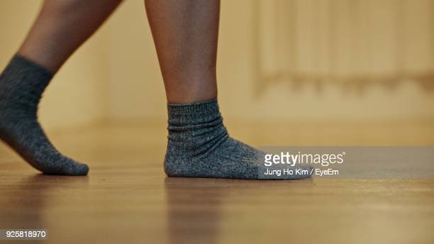 low section of woman in socks on hardwood floor - sock stock pictures, royalty-free photos & images
