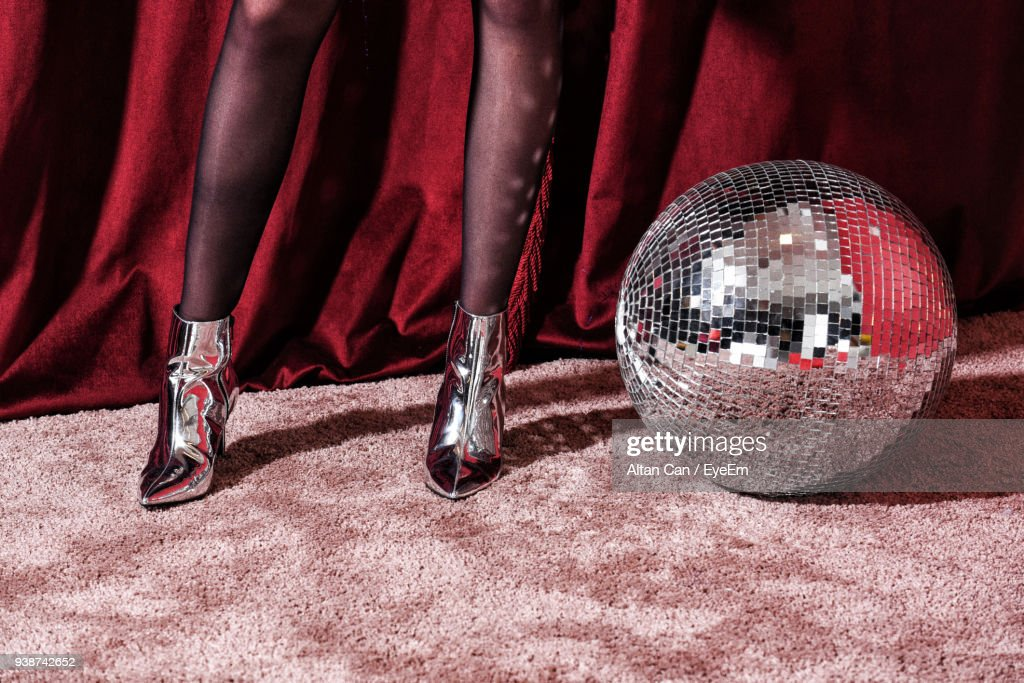 Low Section Of Woman In Stockings Standing By Disco Ball : Stock Photo