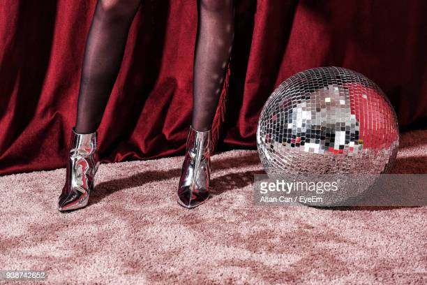 Low Section Of Woman In Stockings Standing By Disco Ball