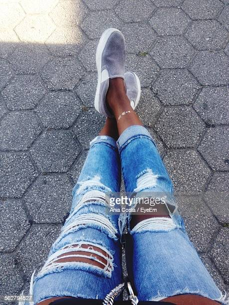 low section of woman in torn jeans relaxing on footpath - trail of tears stock photos and pictures