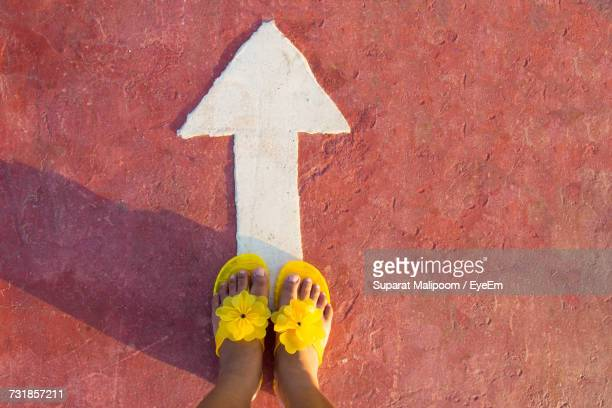 Low Section Of Woman In Yellow Slippers Standing On Street With Arrow Symbol