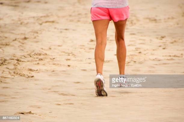 Low Section Of Woman Jogging On Beach
