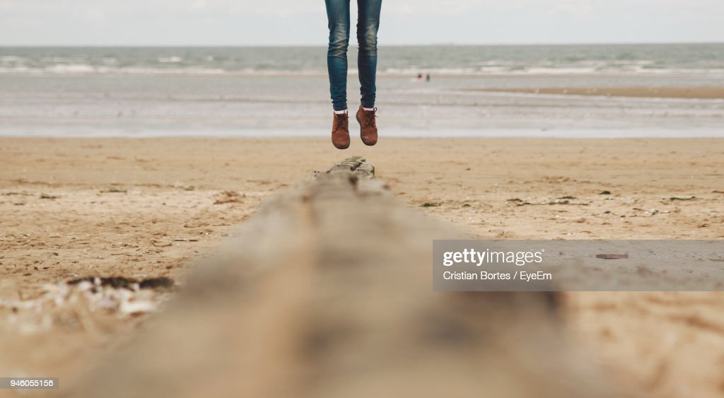 Low Section Of Woman Jumping On Beach : Stock Photo