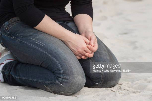 Low Section Of Woman Kneeling On Sand At Beach
