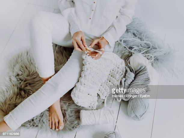 low section of woman knitting wool while sitting at home - stricken stock-fotos und bilder