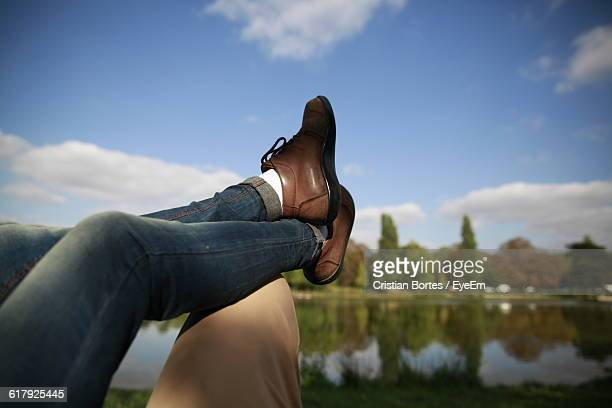 low section of woman legs on man in park against sky - bortes foto e immagini stock