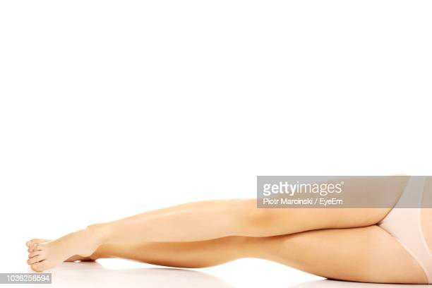 low section of woman lying against white background - セミヌード ストックフォトと画像