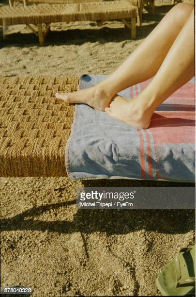 Low Section Of Woman Lying On Camp Bed At Beach