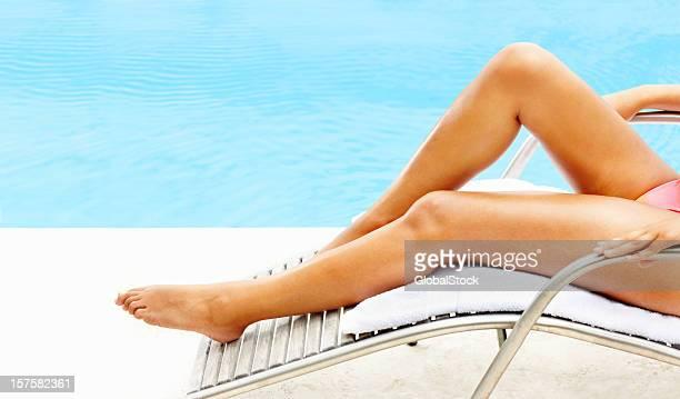 low section of woman lying on recliner by the pool - onderste deel stockfoto's en -beelden