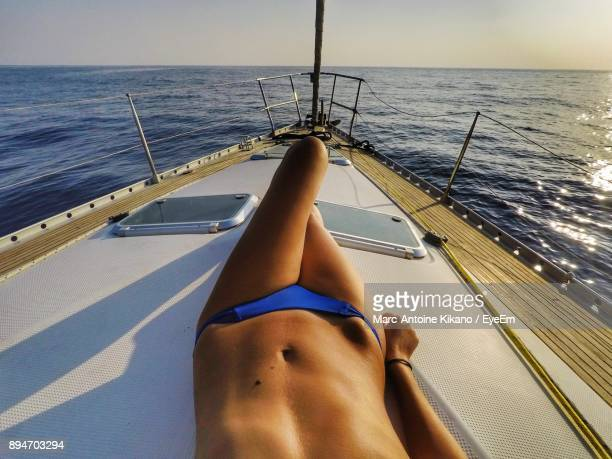 low section of woman lying on yacht against clear sky - partie inférieure photos et images de collection