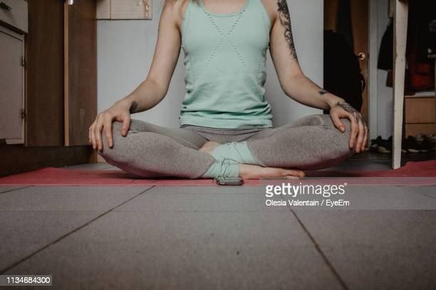 low section of woman meditating while sitting at home - self improvement stock pictures, royalty-free photos & images