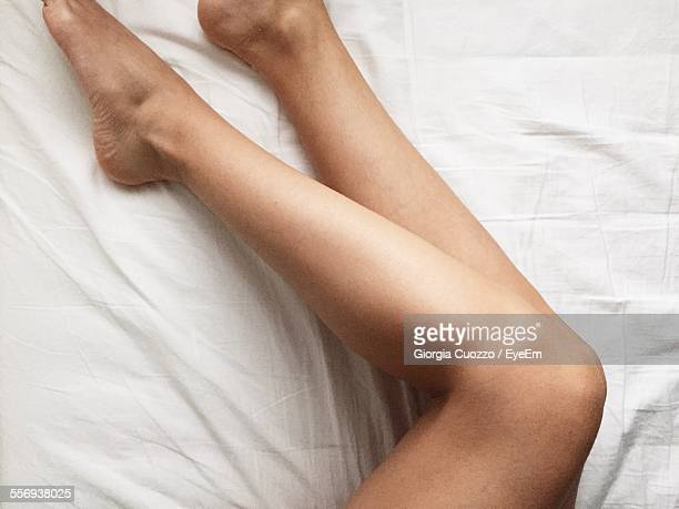 low section of woman on bed - human limb stock pictures, royalty-free photos & images