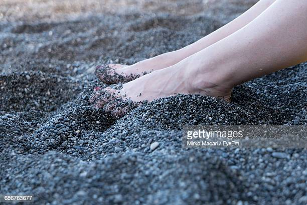 Low Section Of Woman On Black Sand Beach