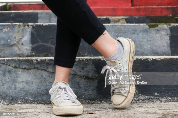 low section of woman on cobblestone street - dirty stock pictures, royalty-free photos & images